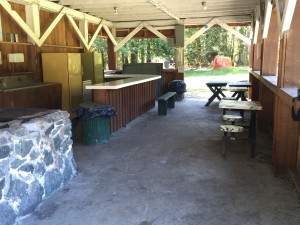 The outdoor kitchen area has two fridges, two stoves, a sink, some tables -- and electricity.
